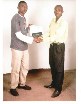 Melvin Udosen, the best A+ Computer and Network Engineering Diploma student receiving his prize - the CompTIA toolkit from Femi Adefeso of Jidaw.com