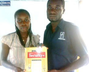 Osunbanjo Fehintola Oluwatobi  receives the Security+ book he won from Saka Babatunde at the November 2010 Free IT Career seminar